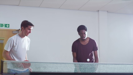 Two men playing table tennis and losing a point