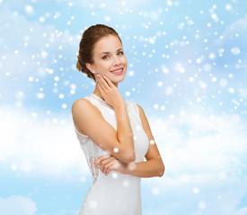 smiling woman in white dress wearing diamond ring