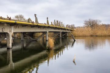 Old ruined bridge over small river