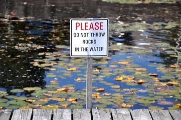 Please do not throw rocks in the water signpost