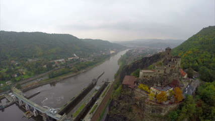 Aerial shot medieval castle, old fortress on river dam, city