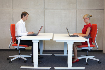 business couple  in correct sitting posture at workstations