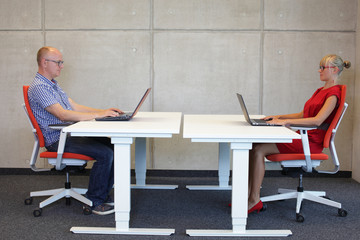 couple in correct sitting posture at workstations  in office