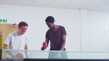 Two male players comically losing a point in table tennis