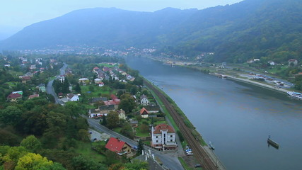 Village alongside river in mountains valley car traffic railroad