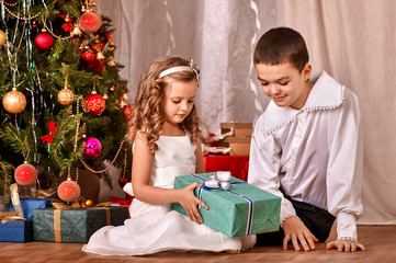 Children  receiving gifts under Christmas tree.