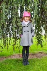 Outdoor portrait of adorable little girl wearing grey coat