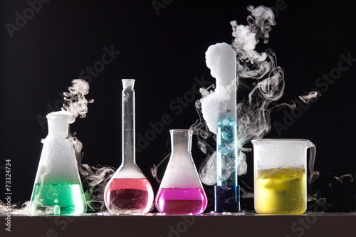 Leinwanddruck Bild Glass in a chemical laboratory filled with colored liquid during