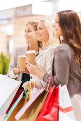 young women with shopping bags and coffee in mall