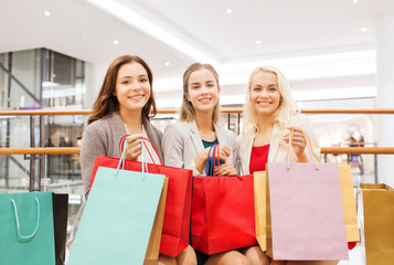 happy young women with shopping bags in mall