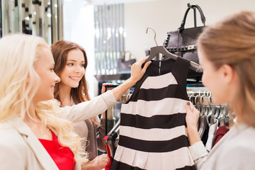 happy young women choosing clothes in mall