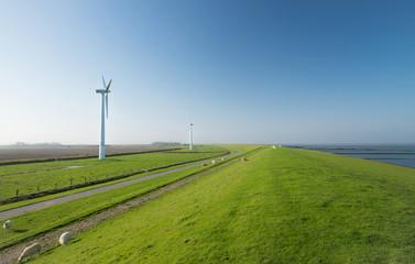 Windräder an der Nordseeküste hinter dem Deich