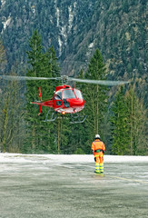 Red helicopter landing at swiss heliport in alps2