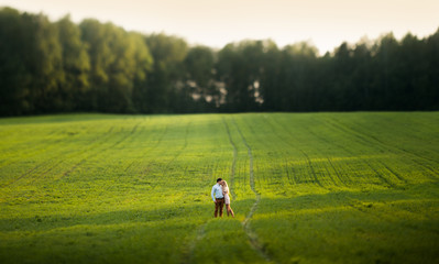 Sensual outdoor portrait of young stylish couple posing in field