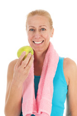 Portrait mature woman at fitness eating an apple