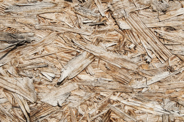 Weathered oriented strand board surface closeup as background