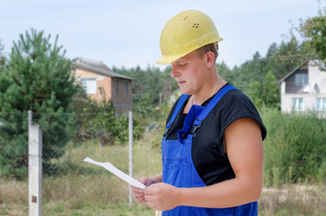 Builder checking paperwork on site