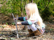 Cute Blond Girl Playing with Twigs on Ground