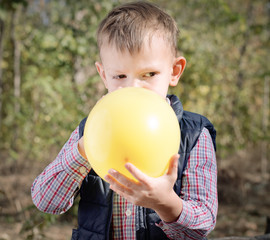 Small boy blowing up a colorful yellow balloon