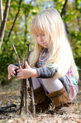 Cute Little Girl Playing with Dry Sticks