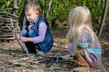 Two young children playing with sticks outdoors