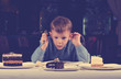 Little boy mesmerised by an assortment of cakes