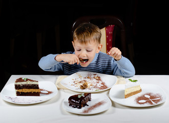 Cute little boy enjoying a treat of party cakes