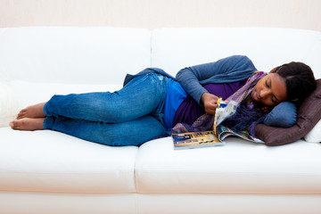 African American woman reading a magazine lying down on the sofa