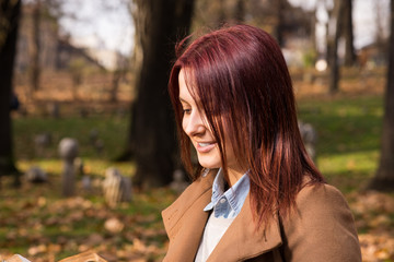 redhead girl sitting on bench in park and reading book