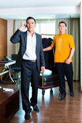 Guest and bell boy standing in hotel room