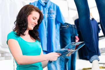 Woman buying fashion blue jeans in shop or store