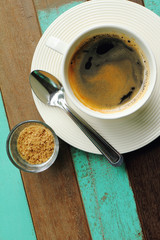 Black coffee in white cup with sugar on old wood background.