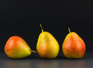Three pears against  dark background
