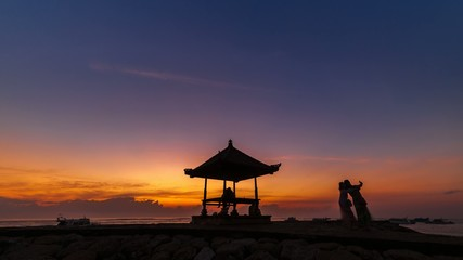 Sunrise time lapse with silhouette of a hut on a beach