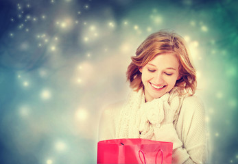 Beautiful young woman looking at a gift bag