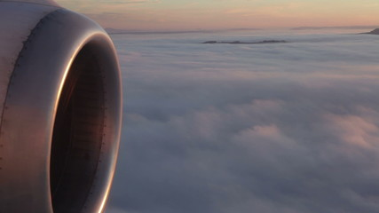 Engine of an airplane flying above clouds in Switzerland.