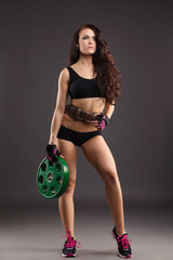 Beautiful female athlete posing with weight disc