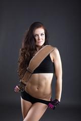 Portrait of cute sporty woman posing with belt