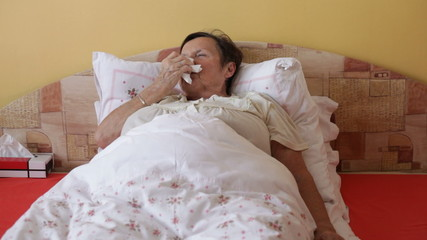 Ill senior woman blowing her nose in bed.