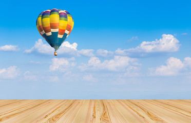 Wood floor and hot air balloon on blue sky