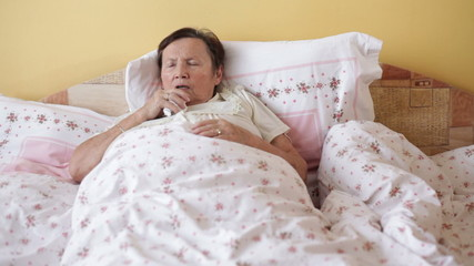 Ill senior woman coughing in bed.