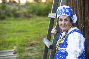 Old woman in Slavic clothing outdoors.