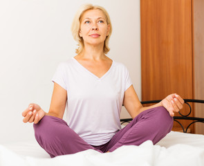 Mature woman doing yoga in bed
