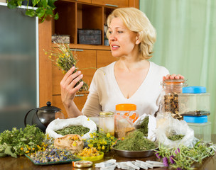 Mature woman with herbs at table