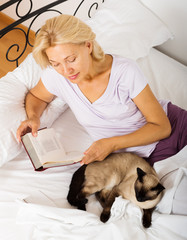 Senior woman with Siamese and book