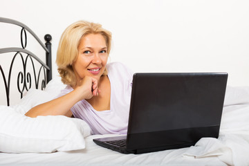 Smiling girl with laptop laying