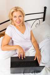 Woman with laptop laying