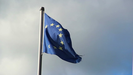 Torn EU European Union flag, dark sky strong wind blowing