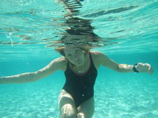 Female with eyes open underwater in ocean