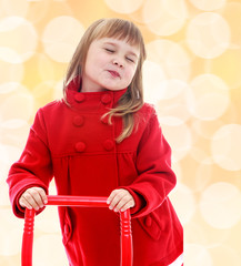 Cute little girl holding a red pen from the cart.